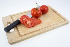 Tomates e faca maduros na placa de corte Fotos de Stock