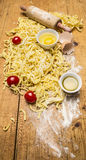 Tomates e massa crus com farinha, ovos e fim rústico de madeira da opinião superior do fundo de sal acima Imagens de Stock Royalty Free
