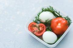 Tomates e ovos maduros no recipiente no fim cinzento do fundo acima Saudável foto de stock royalty free