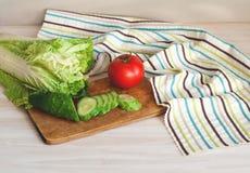 Tomates e pepinos com couve chinesa na tabela para a preparação da salada Fotografia de Stock