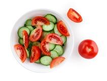 Tomates e pepinos cortados em uma placa branca Fotografia de Stock