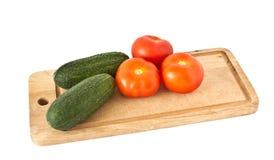 Tomates e pepinos frescos na placa de madeira Foto de Stock
