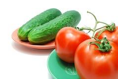 Tomates e pepinos vermelhos na placa Imagens de Stock