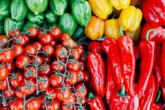 Tomates e pimentas de cereja situados belamente em um ` s m do fazendeiro Fotografia de Stock Royalty Free