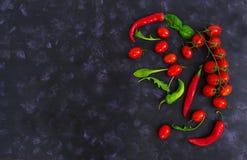 Tomates e pimento maduros frescos de cereja em um fundo escuro Vista superior Imagens de Stock