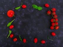 Tomates e pimento maduros frescos de cereja em um fundo escuro Vista superior Fotografia de Stock Royalty Free