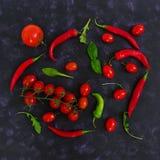 Tomates e pimento maduros frescos de cereja em um fundo escuro Vista superior Fotos de Stock