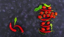Tomates e pimento maduros frescos de cereja em um fundo escuro Vista superior Foto de Stock