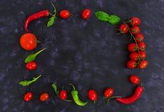 Tomates e pimento maduros frescos de cereja em um fundo escuro Vista superior Fotografia de Stock