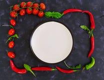 Tomates e pimento maduros frescos de cereja em um fundo escuro Vista superior Imagem de Stock