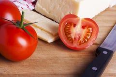Tomates e queijo com a faca na placa de desbastamento Fotografia de Stock