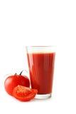 Tomates e suco de tomate vermelhos frescos no vidro isolado em um branco Imagem de Stock