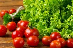 Tomates e vegetais verdes no fundo escuro de madeira Foto de Stock Royalty Free
