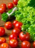 Tomates e vegetais verdes no fundo escuro de madeira Imagens de Stock Royalty Free