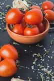 Tomates em um prato em um fundo preto fotografia de stock royalty free
