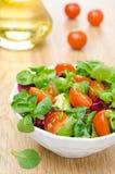 Tomates em uma bacia, azeite da salada e de cereja no fundo Fotos de Stock