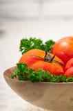 Tomates em uma bacia de madeira Imagem de Stock