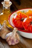 Tomates em uma bacia, em um alho e em um azeite Fotografia de Stock Royalty Free