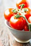 Tomates em uma bacia na tabela de madeira velha Fotos de Stock