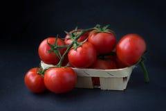 Tomates em uma cesta no fundo preto foto de stock