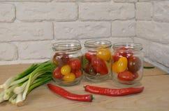 Tomates em umas latas na tabela fotos de stock
