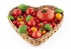 Tomates en cesta en forma de corazón imagen de archivo