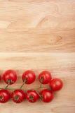 Tomates en el escritorio de madera Imagenes de archivo