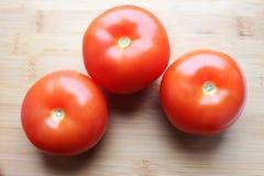 Tomates en el fondo de madera Imagen de archivo libre de regalías