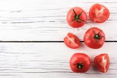 Tomates en el tablero de madera blanco Foto de archivo