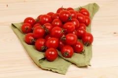 tomates en fondo de madera de la tela verde Fotografía de archivo libre de regalías