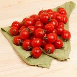 tomates en fondo de madera de la tela verde Foto de archivo libre de regalías