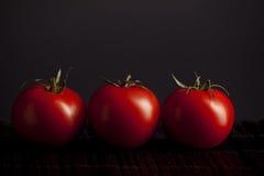 Tomates en fondo negro Fotografía de archivo