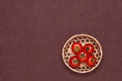 Tomates en la tabla y puestos le en una cesta Fotografía de archivo
