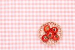 Tomates en la tabla y puestos le en una cesta Foto de archivo