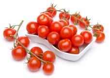 Tomates en un corte blanco y tomates de cereza Fotografía de archivo