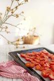 Tomates en un molde para el horno en negro En un fondo ligero Rama de un árbol de la primavera Estilo rural Alimento italiano Foto de archivo