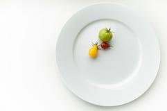 Tomates en una placa Foto de archivo libre de regalías