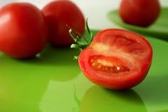 Tomates en una placa verde Imagen de archivo