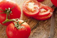 Tomates entières et coupées en tranches sur la vigne Photographie stock