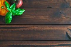 Tomates et basilic d'héritage sur un conseil brun photos libres de droits