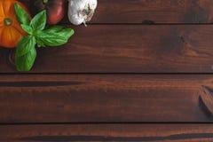 Tomates et basilic d'héritage sur un conseil brun image stock