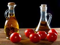 Tomates et bouteilles d'huile d'olive sur la table Image stock