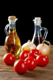 Tomates et bouteilles d'huile d'olive sur la table Photos stock