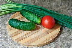 Tomates et concombres rouges frais, oignons verts sur un plateau en bois Photos libres de droits