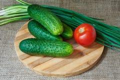 Tomates et concombres rouges frais, oignons verts sur un plateau en bois Photo libre de droits