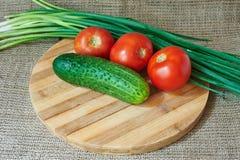 Tomates et concombres rouges frais, oignons verts sur un plateau en bois Images stock