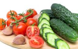 Tomates et concombres sur la planche à découper Photographie stock libre de droits