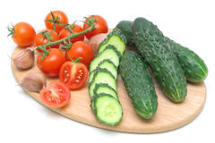 Tomates et concombres sur le panneau de découpage Photographie stock