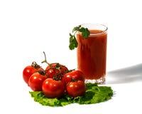 Tomates et jus de tomates d'isolement sur le fond blanc Photographie stock libre de droits