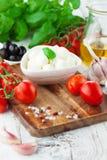 Tomates et mozzarella avec des feuilles de basilic Photographie stock